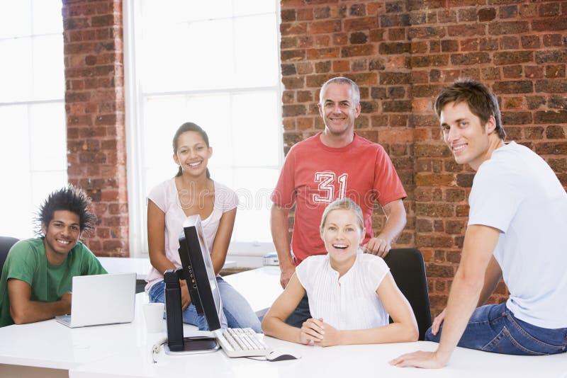 Cinco empresários no sorriso do espaço de escritórios