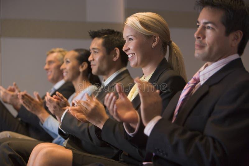 Cinco empresarios que aplauden y que sonríen imagenes de archivo
