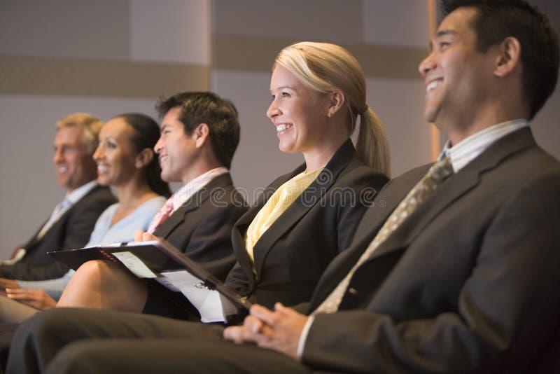Cinco empresarios que sonríen en la presentación foto de archivo libre de regalías