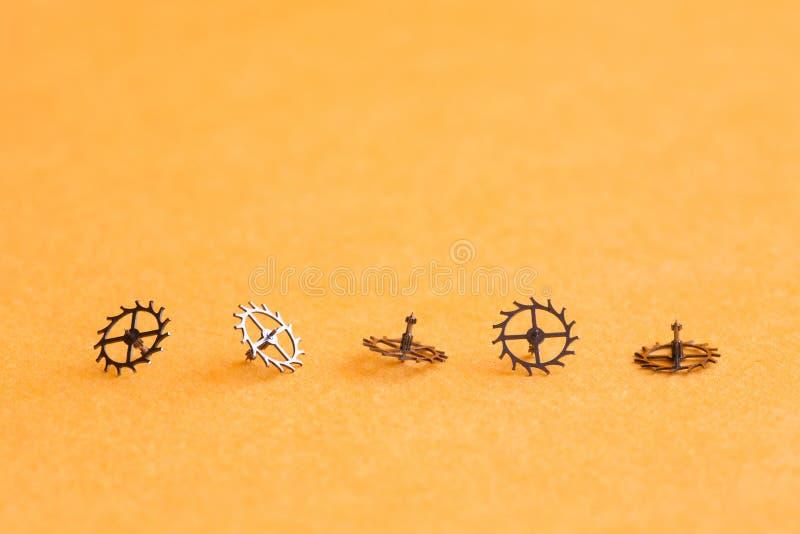 Cinco engrenagens das rodas denteadas no fundo amarelo O relógio de pulso de disparo detalha o close-up, campo da profundidade ra imagem de stock