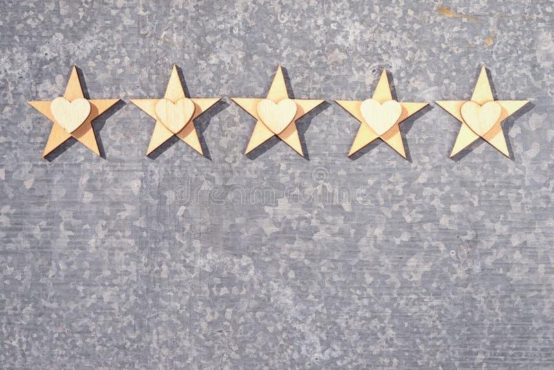 Cinco estrelas e corações de madeira em um fundo estanhar foto de stock royalty free
