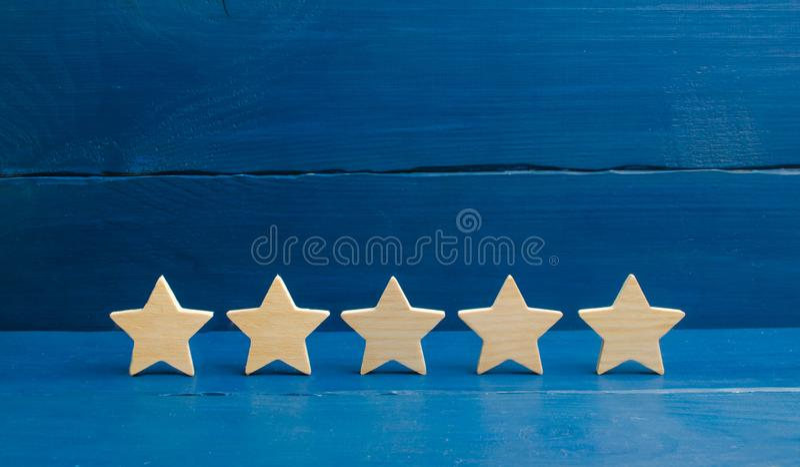 Cinco estrelas em um fundo azul O conceito da avaliação e da avaliação A avaliação do hotel, restaurante, aplicação móvel Qu imagens de stock royalty free