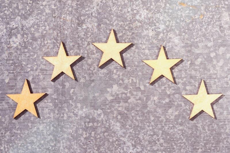 Cinco estrellas de madera en un fondo de la placa de lata foto de archivo
