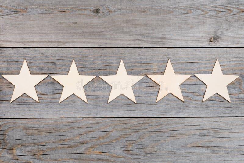 Cinco estrellas en fila en los tablones de madera, concepto de clasificación superior imagen de archivo libre de regalías