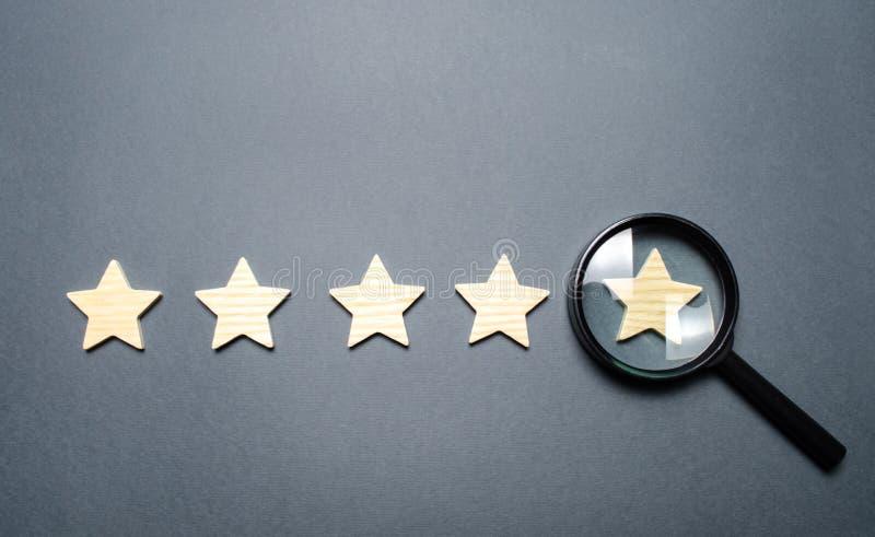 Cinco estrellas y una lupa en la estrella pasada Compruebe la credibilidad del grado o de la situación de la institución, hotel imagen de archivo libre de regalías