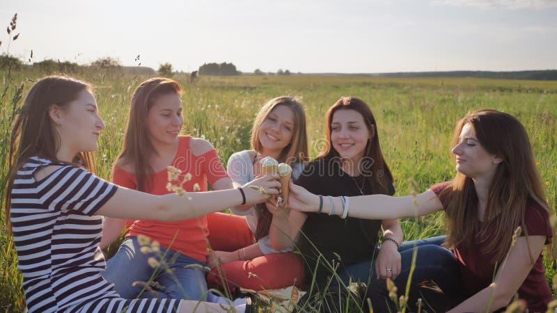 Cinco estudantes novas estão comendo o gelado nas mãos de junta de um prado com gelado imagens de stock