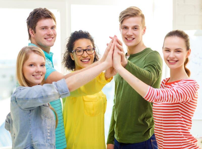 Cinco estudiantes sonrientes que dan el alto cinco en la escuela imagenes de archivo