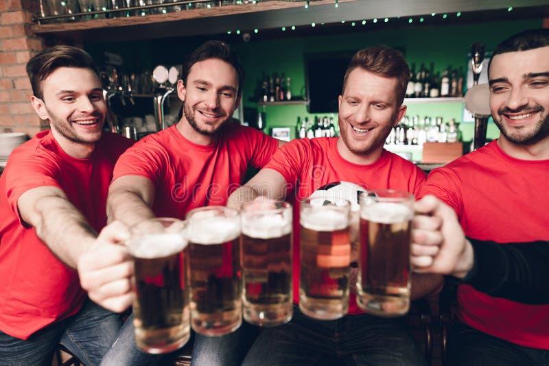 Cinco fãs de esportes que bebem a cerveja que cheering na barra de esportes foto de stock royalty free