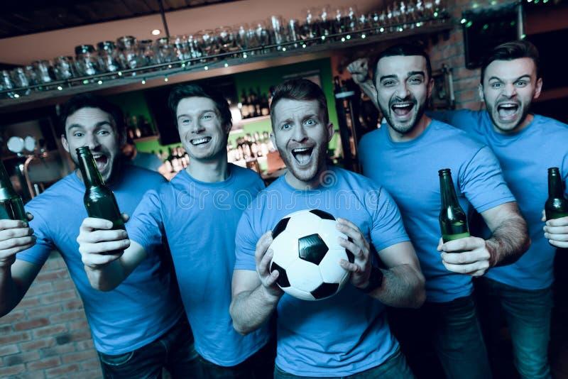 Cinco fãs de esportes que bebem a cerveja que comemora e que cheering na frente da tevê na barra de esportes imagens de stock