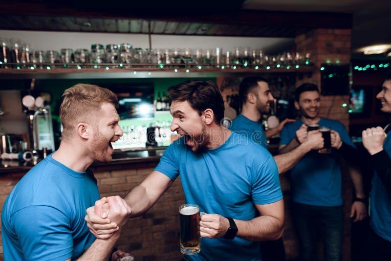 Cinco fãs de esportes que bebem o urso que cheering na barra de esportes Agitando as mãos na celebração foto de stock