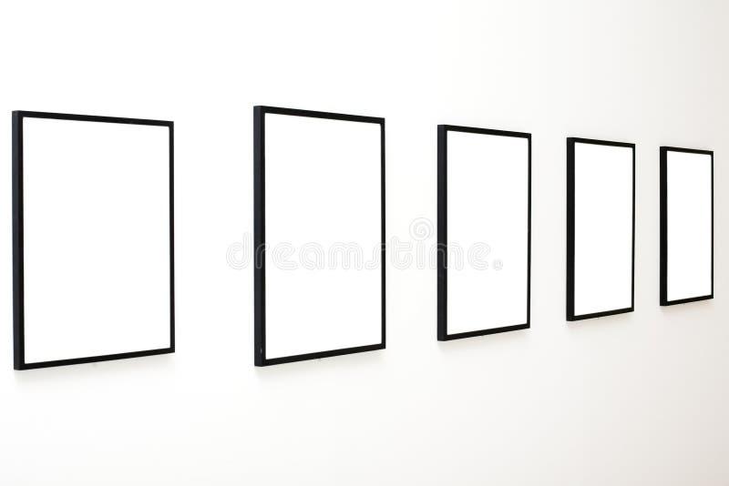 Cinco frames vazios na exposição branca da parede imagens de stock
