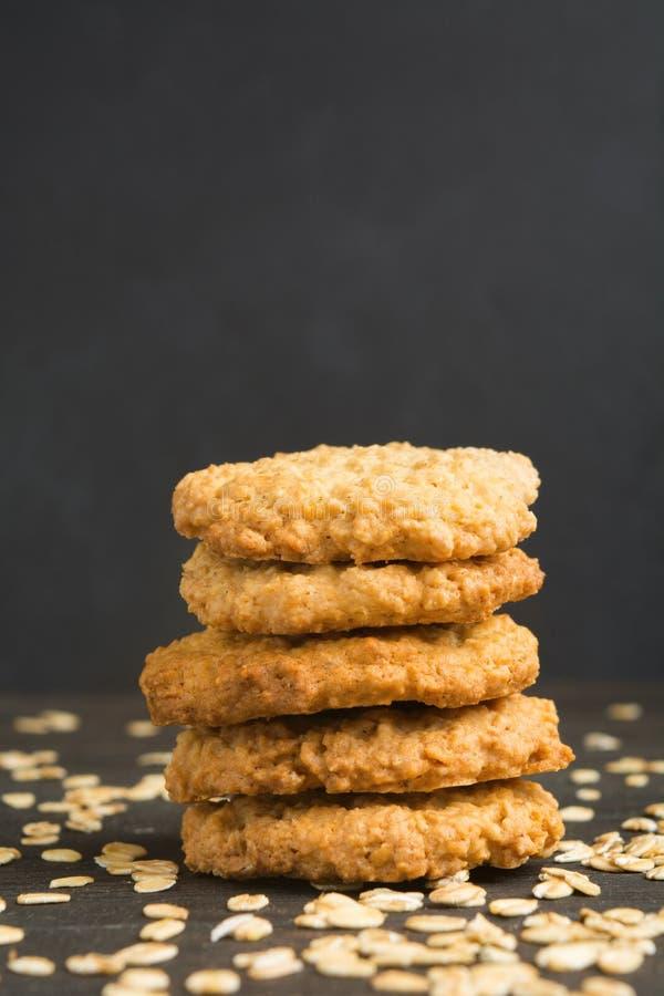 Cinco galletas de harina de avena en pila en fondo oscuro imagen de archivo