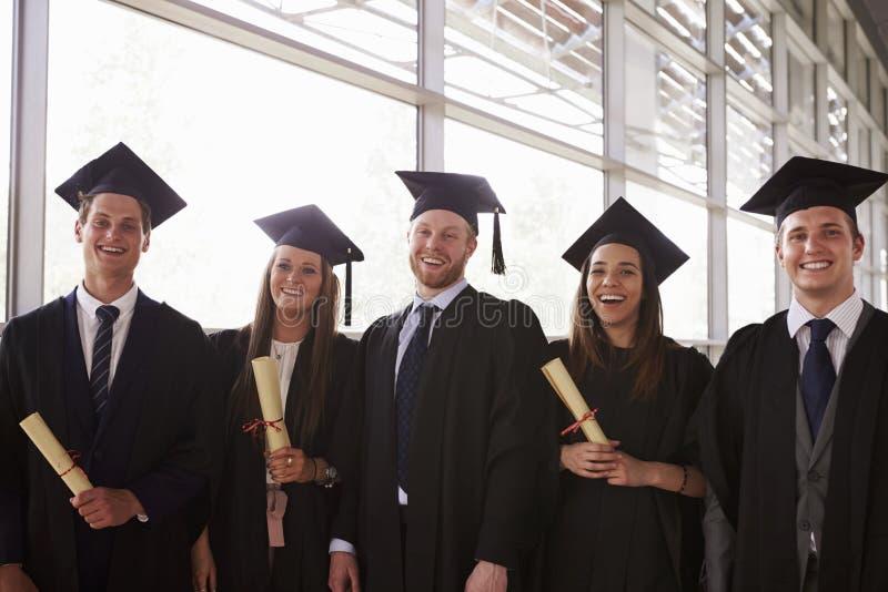 Cinco graduados en los morteros y los vestidos que sostienen certificados fotos de archivo