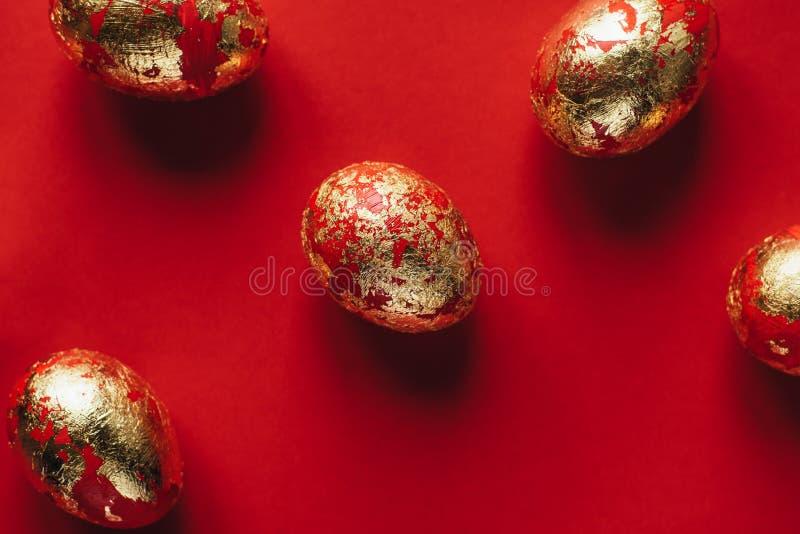 Cinco haber coloreado de oro y adornado con los huevos de Pascua de las chispas en fondo rojo foto de archivo