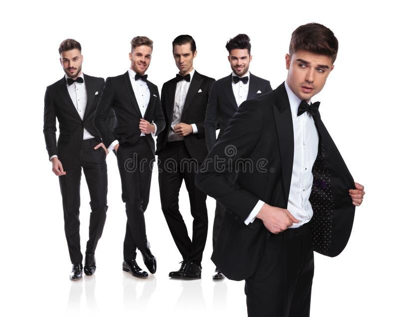 Cinco hombres hermosos en tuxedoes con el líder que mira al lado imagen de archivo