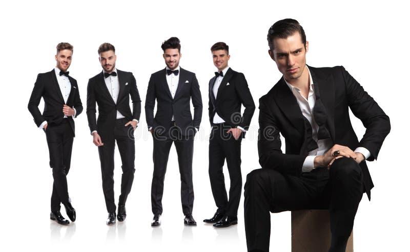 Cinco hombres jovenes en tuxedoes con el líder que se sienta en frente imagen de archivo libre de regalías