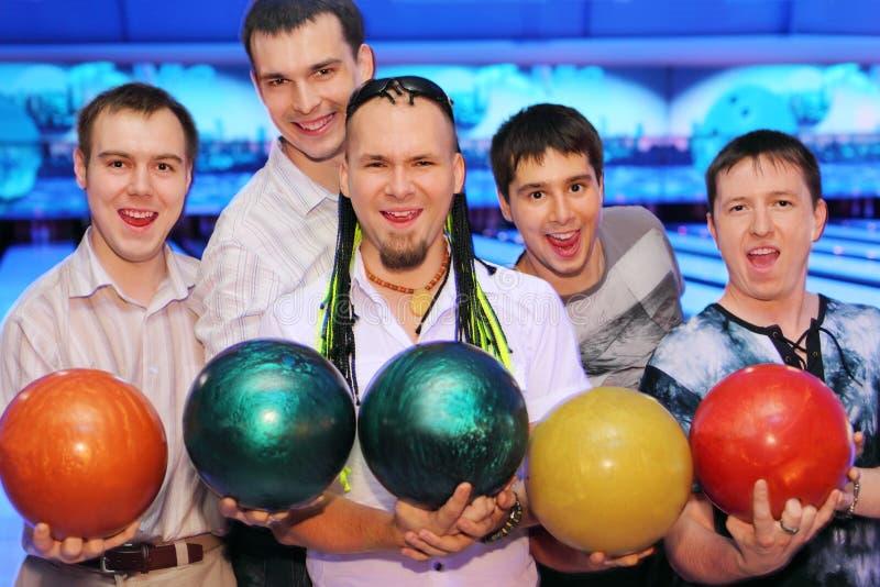 Cinco hombres sostienen bolas en club del bowling fotografía de archivo