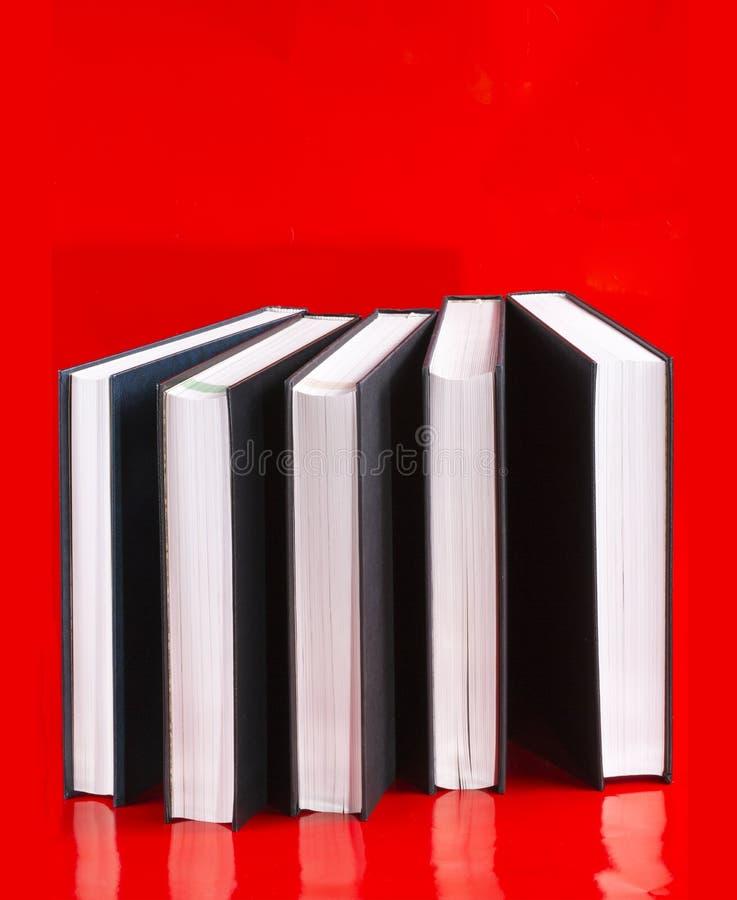 Cinco livros em um vermelho foto de stock royalty free