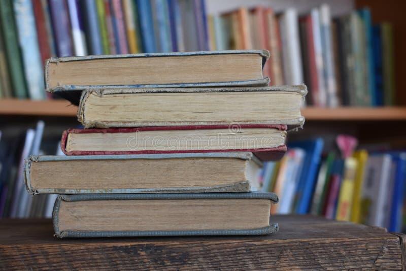 Cinco livros velhos em uma biblioteca imagens de stock