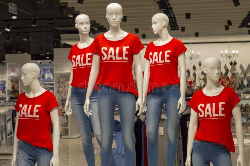 Cinco manequins em seguido vestidos nas calças de brim e em t-shirt vermelhos com as palavras 'VENDA ' fotografia de stock royalty free