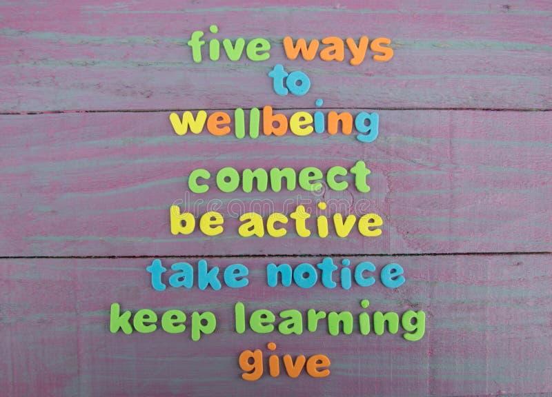 Cinco maneras al bienestar en el fondo de madera del panel fotografía de archivo libre de regalías