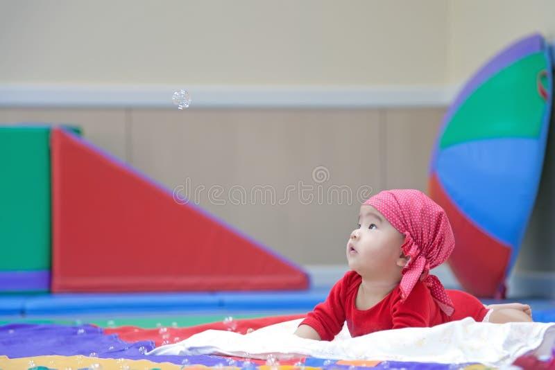 Cinco meses bonitos do bebê asiático que olha a bolha de sabão imagem de stock