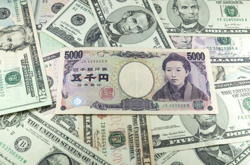 Cinco mil notas do iene japonês no fundo de muitos dólares fotos de stock