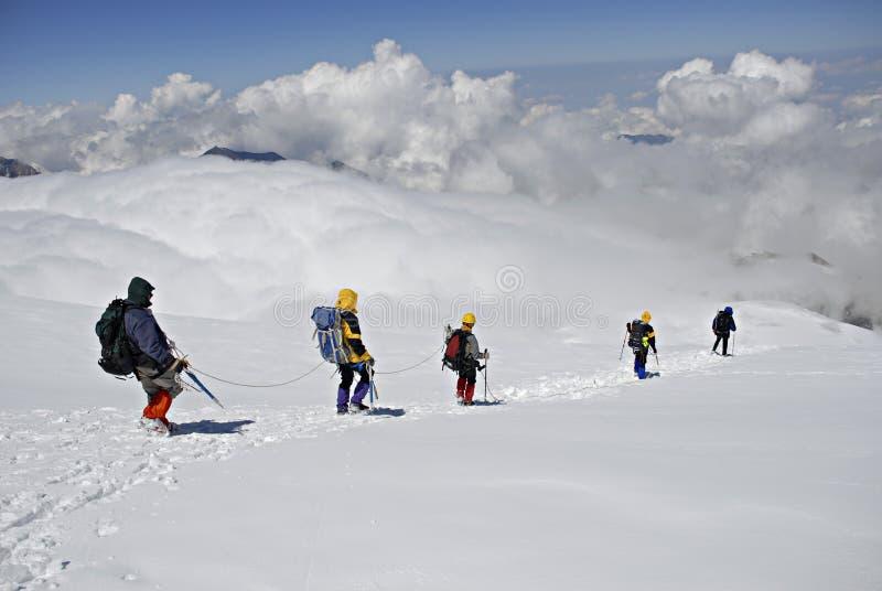 Cinco montanhistas que trekking para baixo imagem de stock