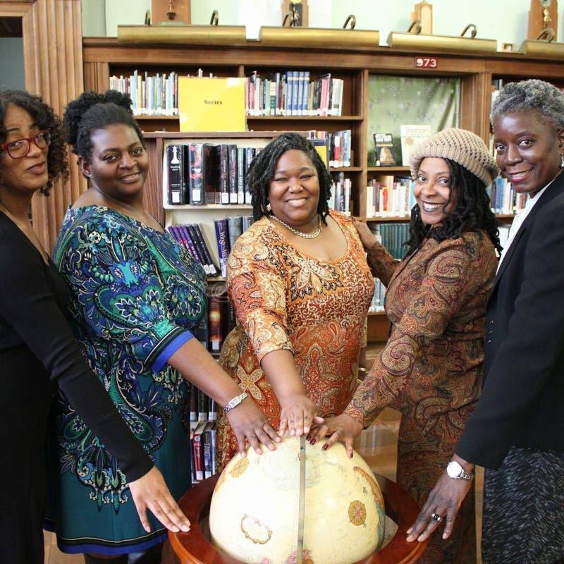 Cinco mujeres con las manos encima de un globo de madera foto de archivo