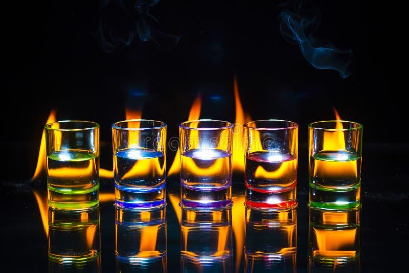 Cinco multicolores de los vasos de medida de las bebidas reflejaron por completo en el g fotos de archivo libres de regalías