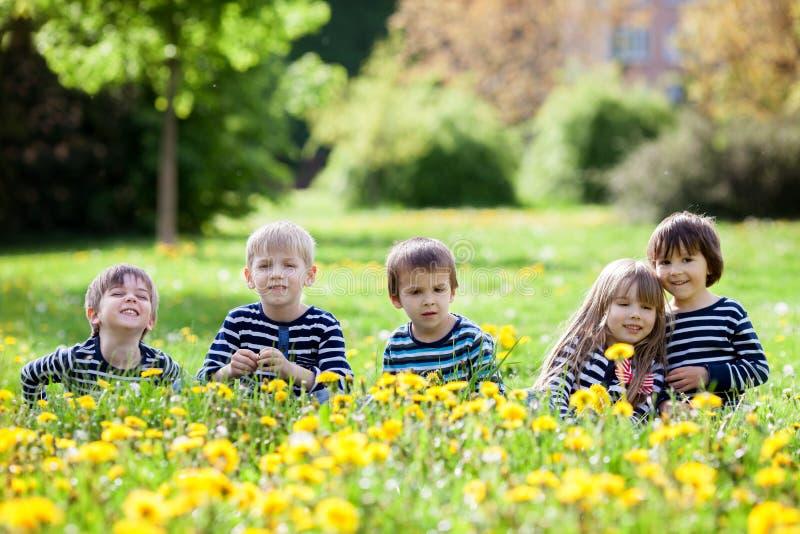 Cinco niños adorables, vestidos en camisas rayadas, el abrazo y el smili imagenes de archivo