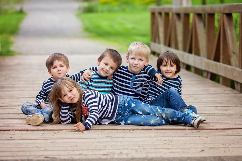 Cinco niños adorables, vestidos en las camisas rayadas, sentándose en un brid imagen de archivo