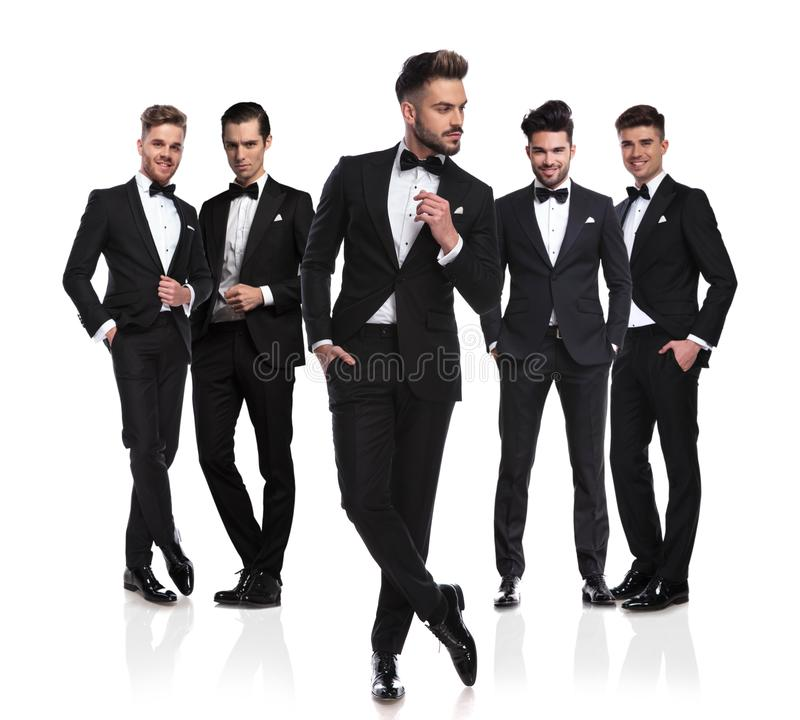 Cinco novios en tuxedoes negros con el líder pensativo en frente imagenes de archivo