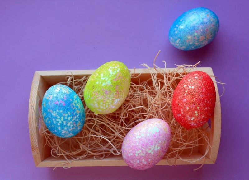 Cinco ovos da páscoa coloridos na caixa de assentamento no fundo roxo imagem de stock royalty free