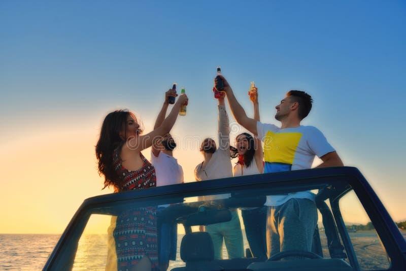 Cinco personas jovenes que se divierten en coche convertible en la playa en la puesta del sol imagen de archivo libre de regalías