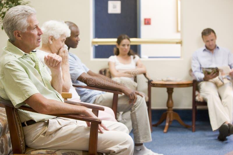 Cinco personas que esperan en sala de espera imágenes de archivo libres de regalías
