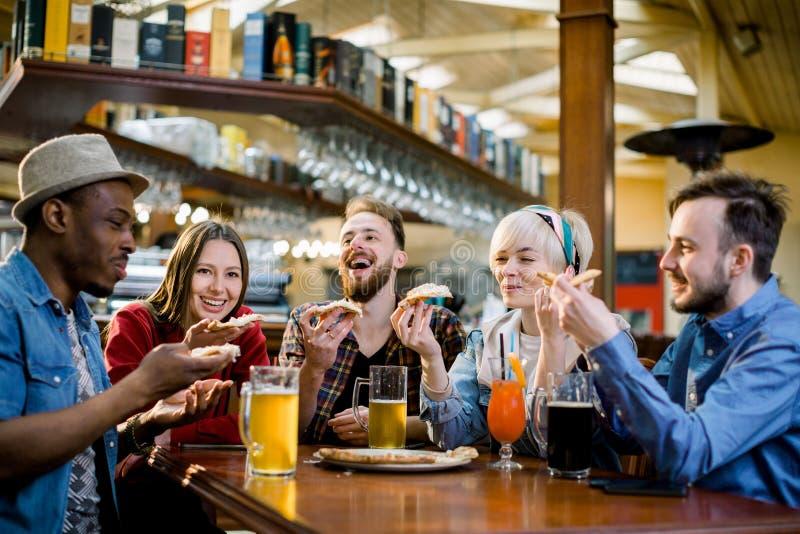 Cinco pessoas novas que comem a pizza e que riem ao sentar-se em um restaurante do fast food Grupo de amigos que apreciam o quand fotos de stock