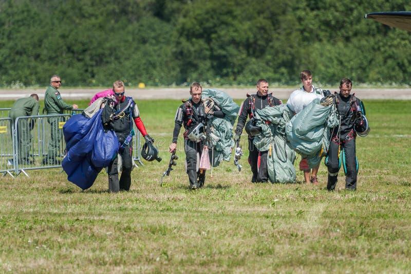Cinco skydivers estão compartilhando de emoções após o salto e a aterrissagem fotos de stock