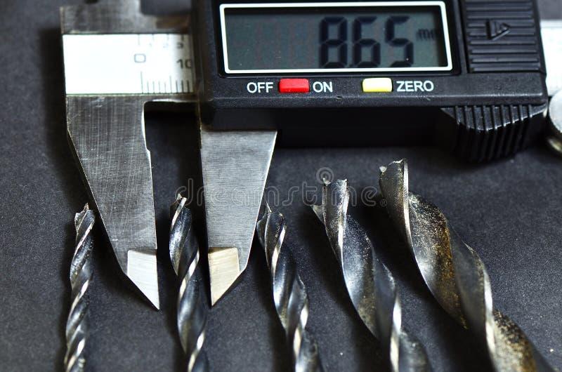 Cinco taladros y un calibrador digital foto de archivo libre de regalías