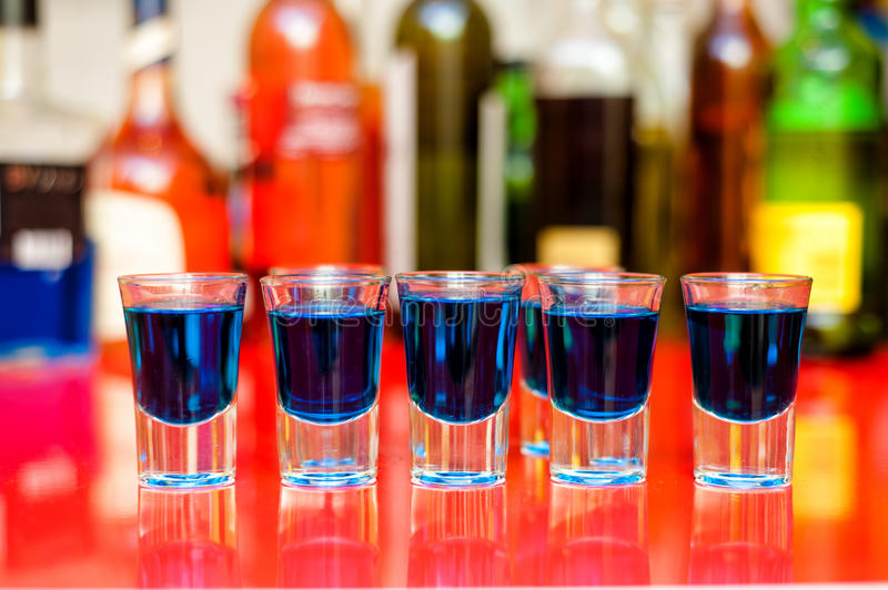 Cinco tiros alcohólicos azules de curaçao en barra foto de archivo