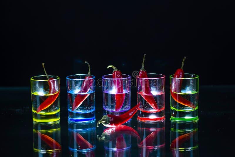 Cinco vasos de medida multicolores llenos de bebida y con el ch rojo fotografía de archivo