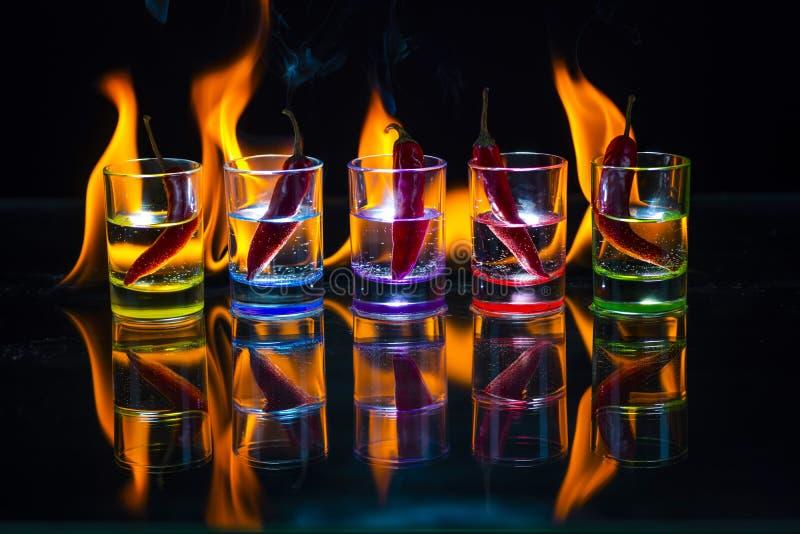 Cinco vasos de medida multicolores llenos de bebida y con el ch rojo imagen de archivo libre de regalías