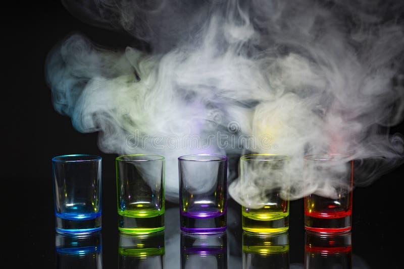Cinco vasos de medida vacíos multicolores colocados simétricamente en un b imágenes de archivo libres de regalías