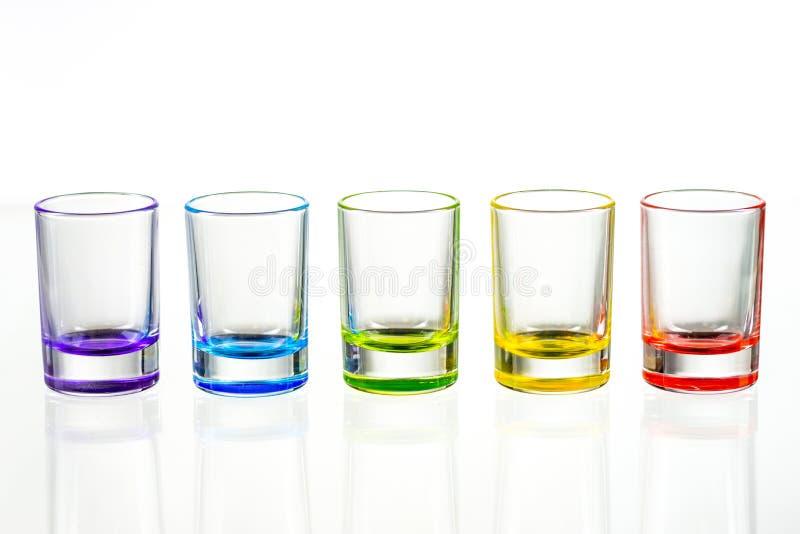 Cinco vasos de medida vacíos multicolores colocados simétricamente en un w imágenes de archivo libres de regalías