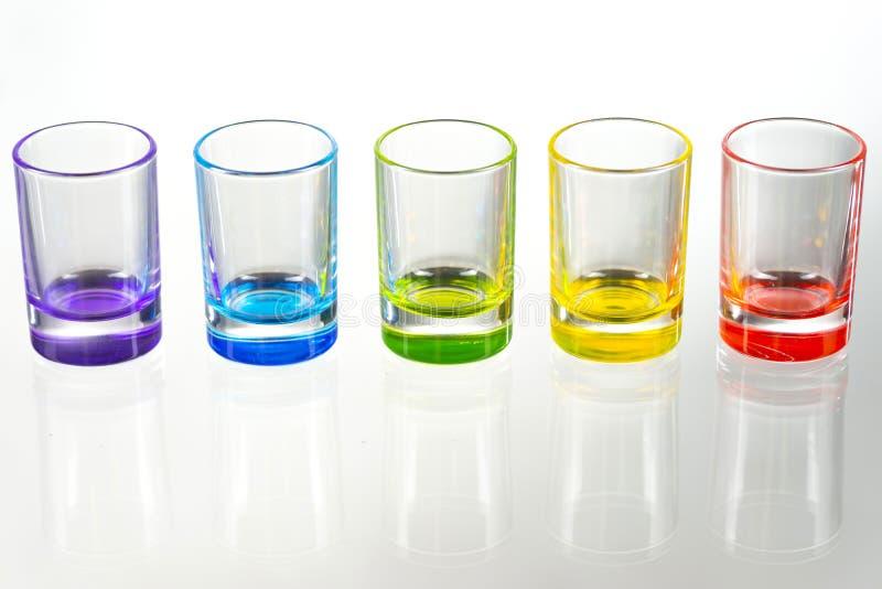 Cinco vasos de medida vacíos multicolores colocados simétricamente en un w imagen de archivo libre de regalías
