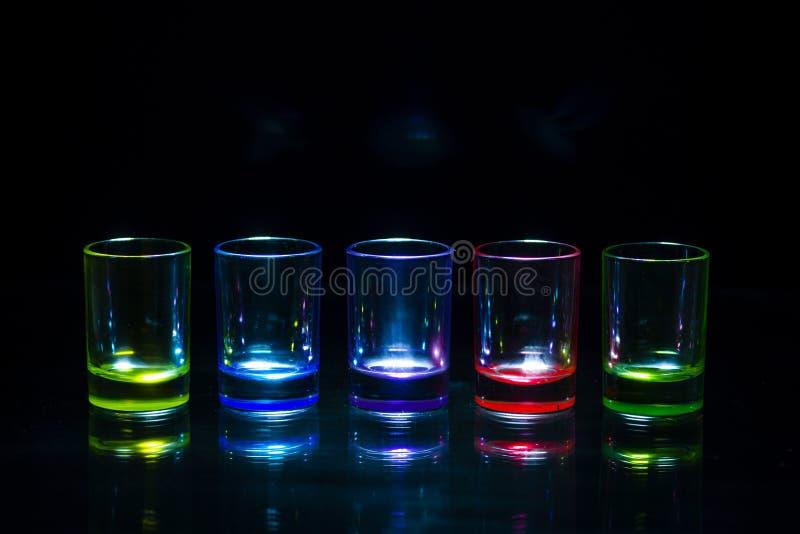 Cinco vasos de medida vacíos multicolores que reflejan en un surfa de cristal imagen de archivo libre de regalías