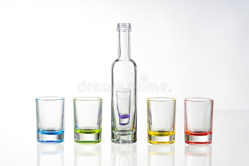 Cinco vasos de medida vacíos multicolores y la pequeña botella pusieron el sym foto de archivo libre de regalías