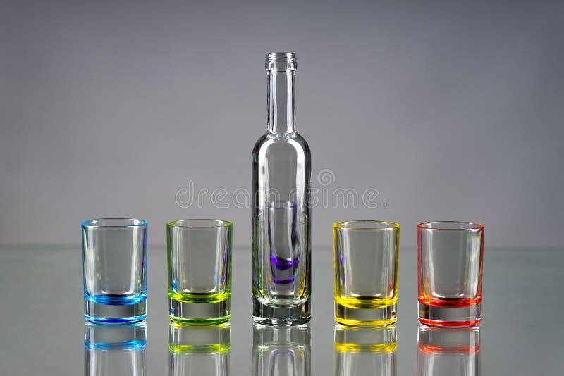Cinco vasos de medida vacíos multicolores y la pequeña botella pusieron el sym fotos de archivo