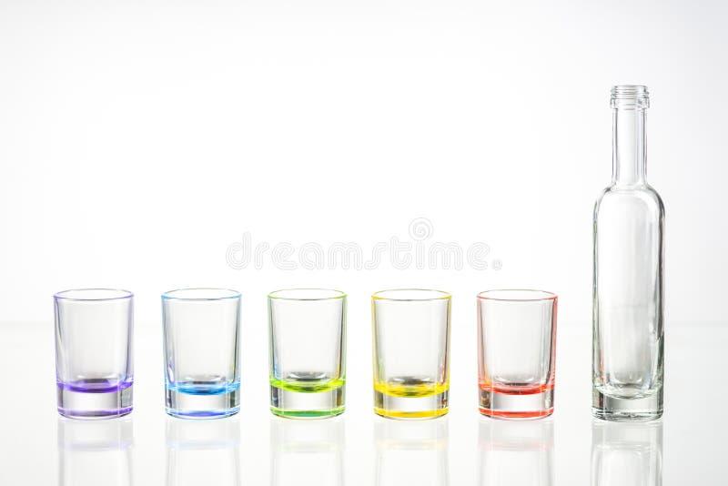 Cinco vasos de medida vacíos multicolores y la pequeña botella pusieron uns imagenes de archivo