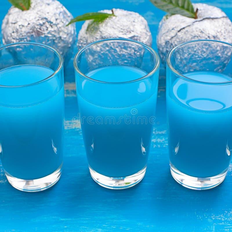 Cinco vidrios del surrealismo azul Apple de la bebida Foil el fondo lamentable azul foto de archivo libre de regalías